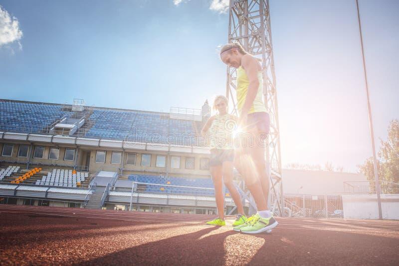 Θηλυκός αθλητής sprinter δύο που φορούν την μπλούζα και σορτς που στέκονται σε μια κόκκινη τρέχοντας διαδρομή στο στάδιο αθλητισμ στοκ εικόνες