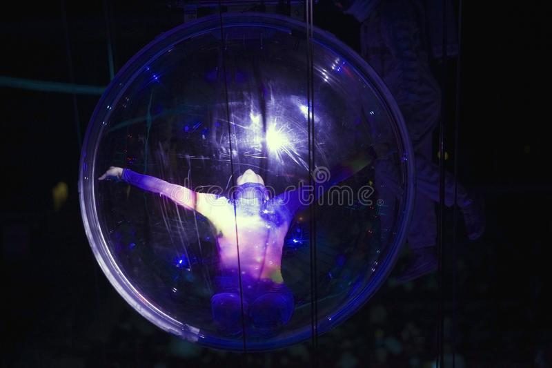 Θηλυκός ακροβάτης στη σφαίρα που αποδίδει στο κέντρο της Barclays για στοκ εικόνες