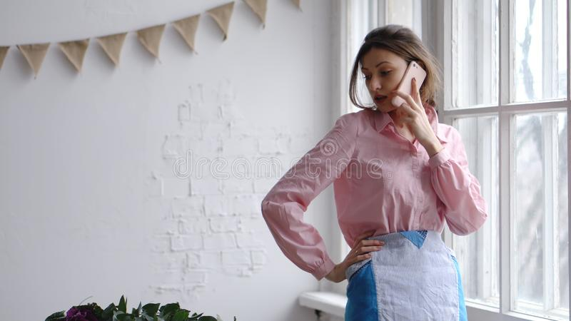 Θηλυκός ανθοκόμος που μιλά στα κινητά λουλούδια τηλεφώνων και επιθεώρησης στοκ φωτογραφία
