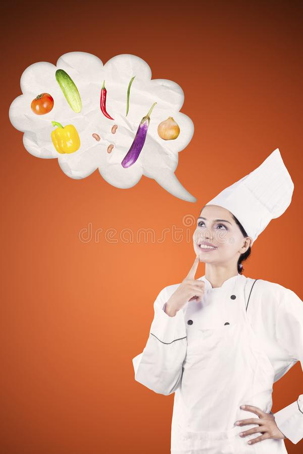 Θηλυκός αρχιμάγειρας που σκέφτεται νέα τη συνταγή της στοκ εικόνες
