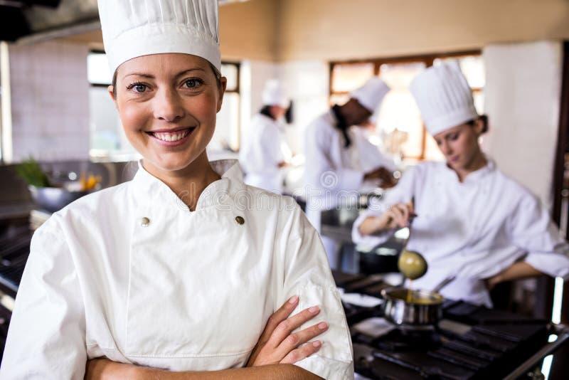 Θηλυκός αρχιμάγειρας που στέκεται με τα όπλα που διασχίζονται στην κουζίνα στοκ εικόνες με δικαίωμα ελεύθερης χρήσης