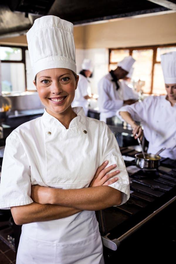 Θηλυκός αρχιμάγειρας που στέκεται με τα όπλα που διασχίζονται στην κουζίνα στοκ φωτογραφίες με δικαίωμα ελεύθερης χρήσης