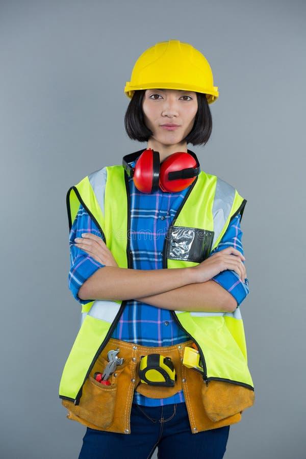 Θηλυκός αρχιτέκτονας που στέκεται με τα όπλα που διασχίζονται στο γκρίζο κλίμα στοκ φωτογραφία