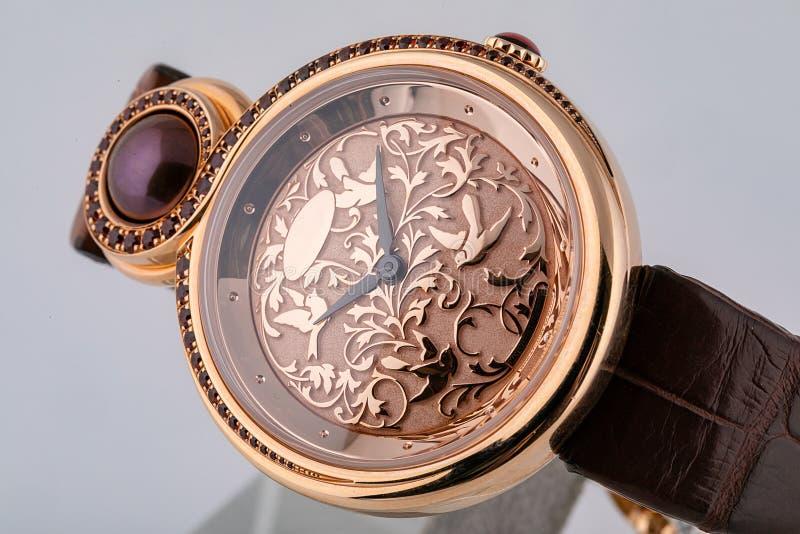 Θηλυκός αυξήθηκε χρυσός wristwatch με τον ανοικτό ροζ πίνακα με ένα σχέδιο, ο Μαύρος δεξιόστροφα, στο καφετί λουρί δέρματος στο ά στοκ φωτογραφίες
