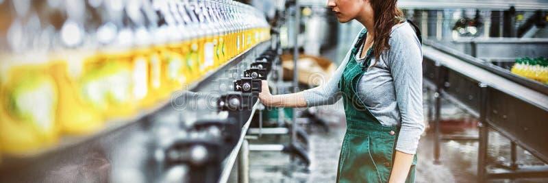 Θηλυκός βιομηχανικός εργάτης που στέκεται κοντά στη γραμμή παραγωγής στοκ εικόνες