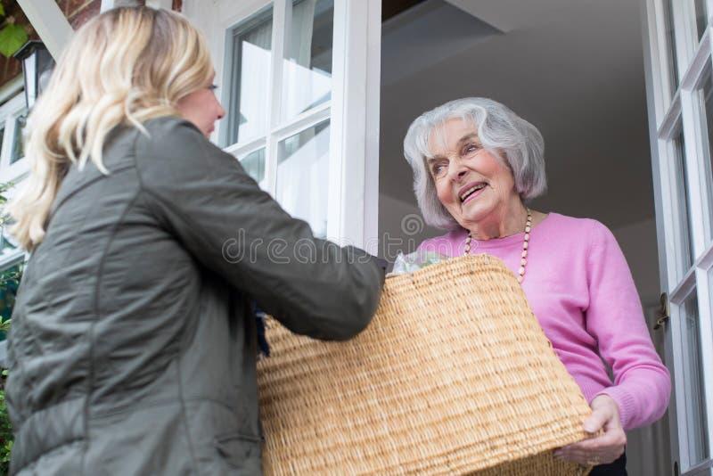 Θηλυκός γείτονας που βοηθά την ανώτερη γυναίκα με τις αγορές στοκ φωτογραφία με δικαίωμα ελεύθερης χρήσης