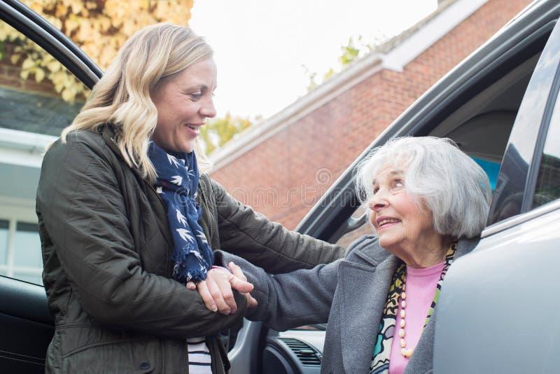 Θηλυκός γείτονας που δίνει στην ανώτερη γυναίκα έναν ανελκυστήρα στο αυτοκίνητο στοκ εικόνα