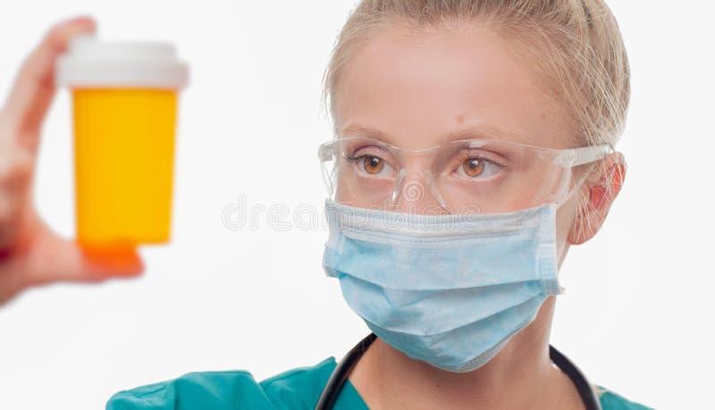 Θηλυκός γιατρός, νοσοκόμα που κρατά ένα μπουκάλι των χαπιών στο άσπρο υπόβαθρο στοκ εικόνα