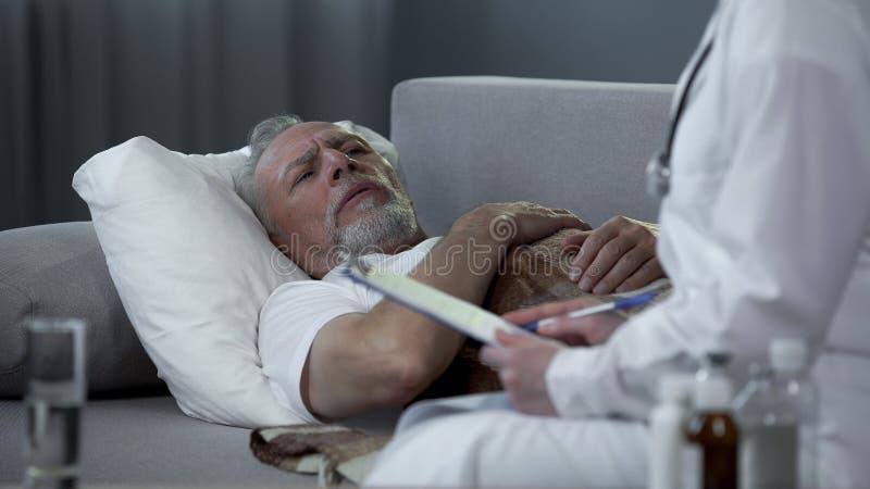 Θηλυκός γιατρός που ορίζει τα φάρμακα στον άρρωστο ηληκιωμένο που βρίσκεται στο κρεβάτι στο σπίτι στοκ φωτογραφία με δικαίωμα ελεύθερης χρήσης