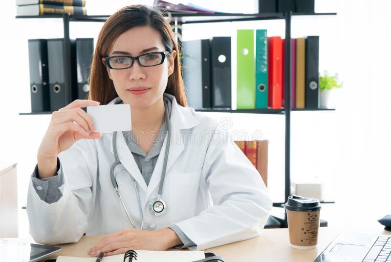 Θηλυκός γιατρός που παρουσιάζει κενή κάρτα στοκ φωτογραφία με δικαίωμα ελεύθερης χρήσης