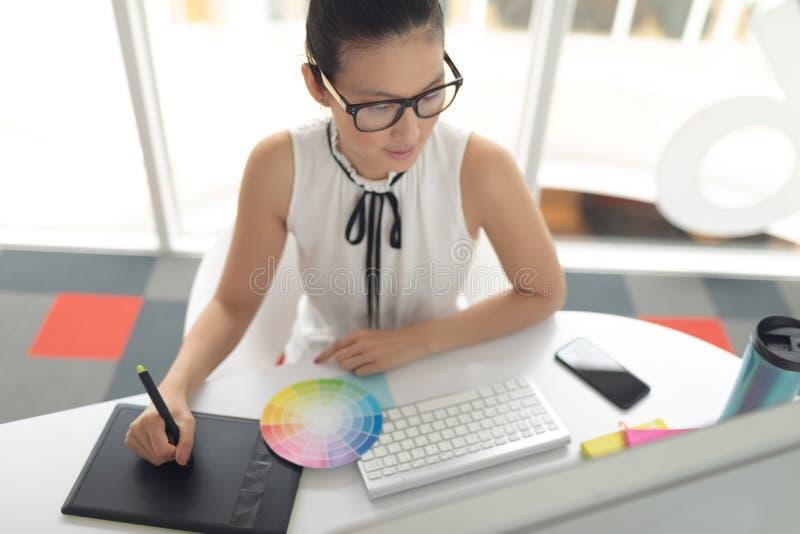 Θηλυκός γραφικός σχεδιαστής που χρησιμοποιεί τη γραφική ταμπλέτα στο γραφείο σε ένα σύγχρονο γραφείο στοκ εικόνα