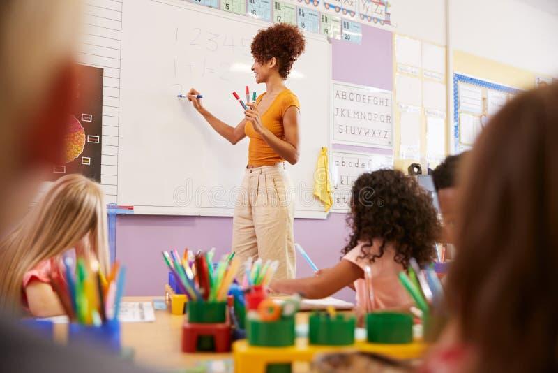 Θηλυκός δάσκαλος που στέκεται στο μάθημα μαθηματικών διδασκαλίας Whiteboard στους στοιχειώδεις μαθητές στη σχολική τάξη στοκ φωτογραφία με δικαίωμα ελεύθερης χρήσης