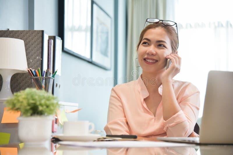 Θηλυκός δημιουργικός σχεδιαστής που μιλά στο τηλέφωνο κυττάρων στον εργασιακό χώρο της στοκ φωτογραφίες