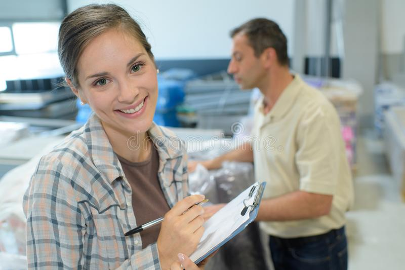 Θηλυκός διευθυντής αποθηκών εμπορευμάτων που ελέγχει τον κατάλογο στη μεγάλη αποθήκη εμπορευμάτων στοκ φωτογραφίες με δικαίωμα ελεύθερης χρήσης