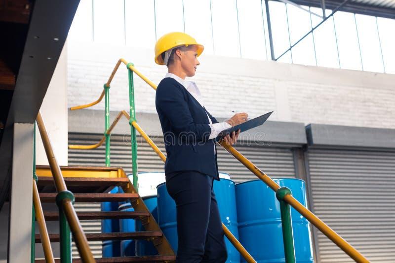 Θηλυκός διευθυντής που γράφει στην περιοχή αποκομμάτων στα σκαλοπάτια στην αποθήκη εμπορευμάτων στοκ φωτογραφίες με δικαίωμα ελεύθερης χρήσης