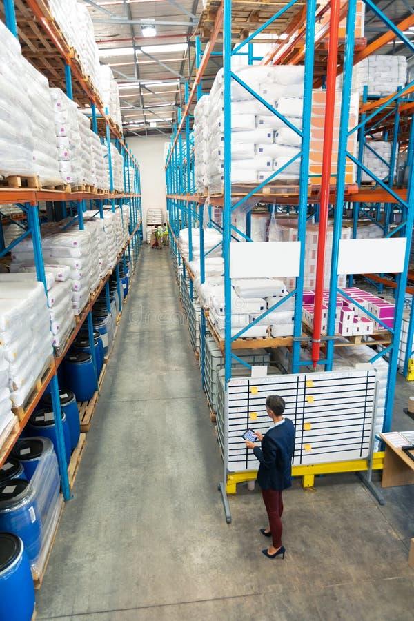 Θηλυκός διευθυντής που εργάζεται στο λευκό πίνακα στην αποθήκη εμπορευμάτων στοκ φωτογραφία με δικαίωμα ελεύθερης χρήσης