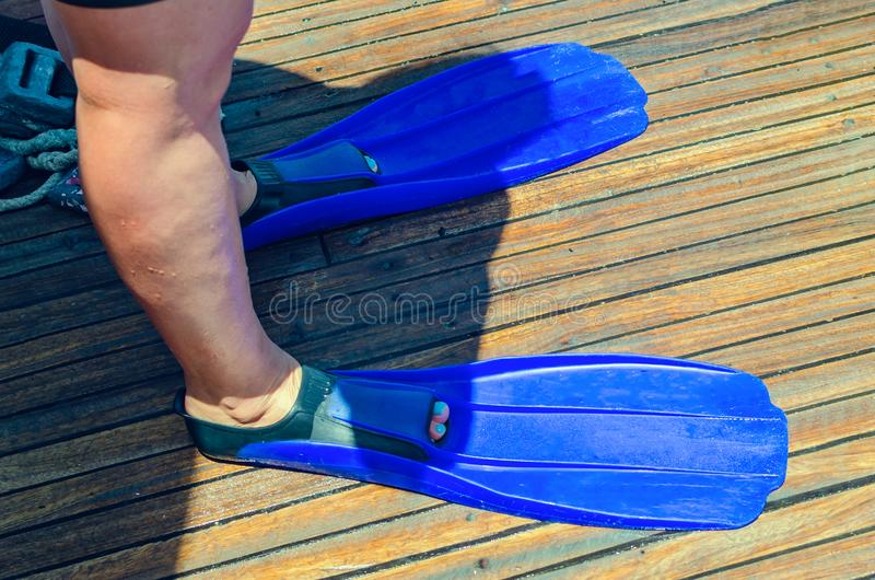 Θηλυκός δύτης σκαφάνδρων που στέκεται στα βατραχοπέδιλα στη βάρκα πρίν βουτά στοκ φωτογραφία με δικαίωμα ελεύθερης χρήσης