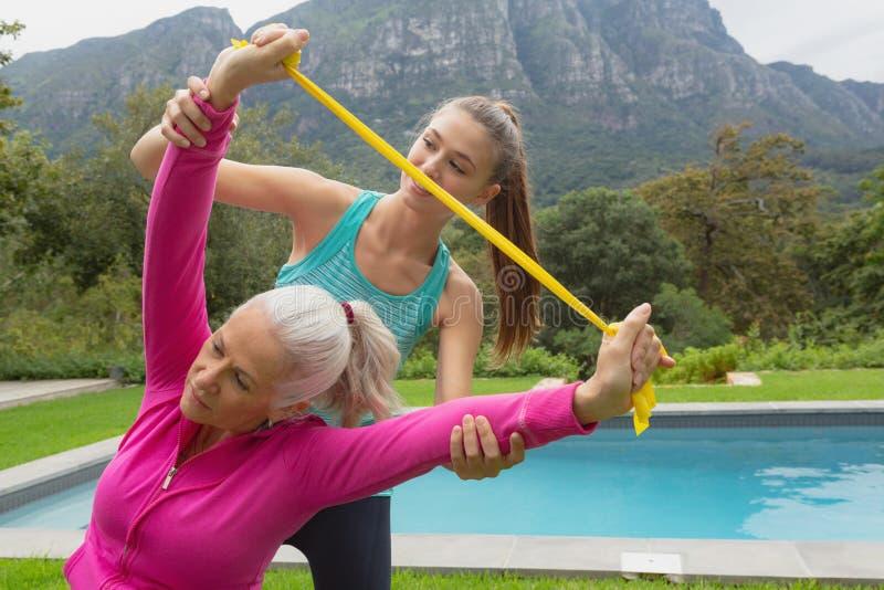 Θηλυκός εκπαιδευτής που βοηθά την ενεργό ανώτερη γυναίκα στην άσκηση με τη ζώνη αντίστασης στοκ φωτογραφία με δικαίωμα ελεύθερης χρήσης