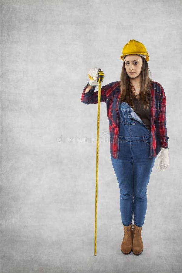 Θηλυκός εργάτης οικοδομών με το μετρητή, διάστημα αντιγράφων στοκ φωτογραφία