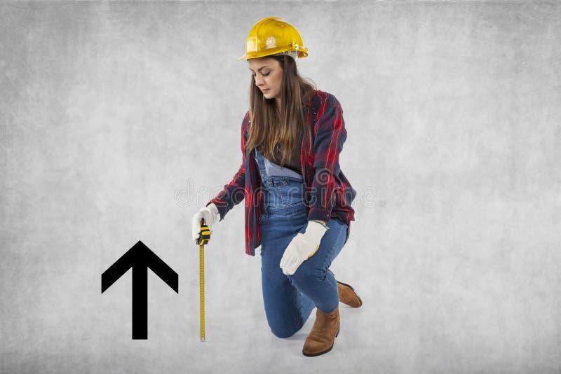 Θηλυκός εργάτης οικοδομών που γονατίζει δίπλα στο βέλος στοκ φωτογραφία με δικαίωμα ελεύθερης χρήσης
