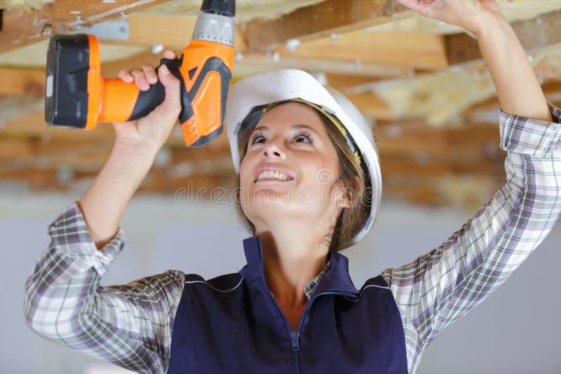 Θηλυκός εργάτης οικοδομών που χρησιμοποιεί το ασύρματο τρυπάνι στοκ φωτογραφία με δικαίωμα ελεύθερης χρήσης