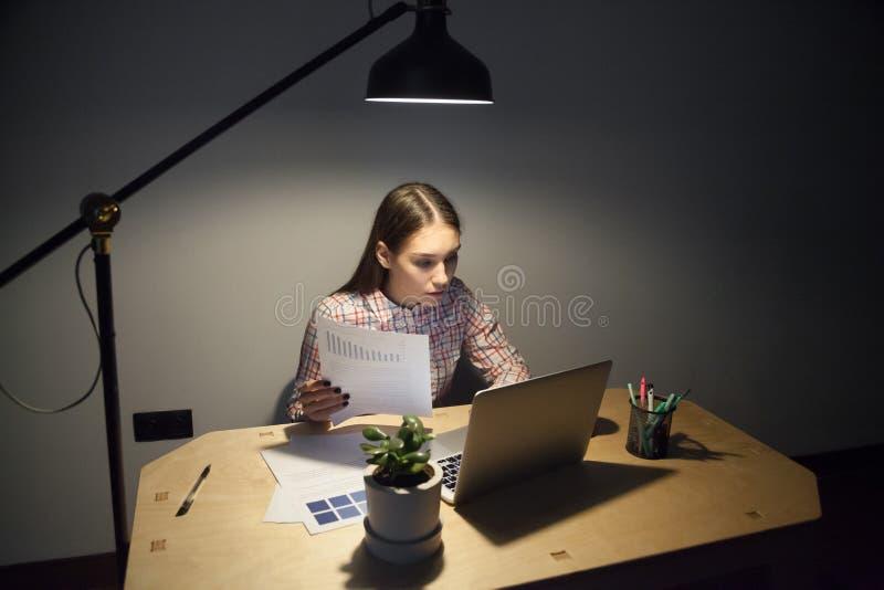Θηλυκός εταιρικός διευθυντής που συγκρίνει τα στοιχεία στο έγγραφο με την επιχείρηση στοκ εικόνα