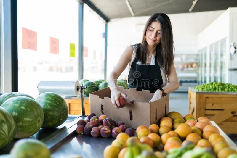 Θηλυκός ιδιοκτήτης που επιδεικνύει τα φρέσκα ροδάκινα στο κατάστημα στοκ εικόνα με δικαίωμα ελεύθερης χρήσης