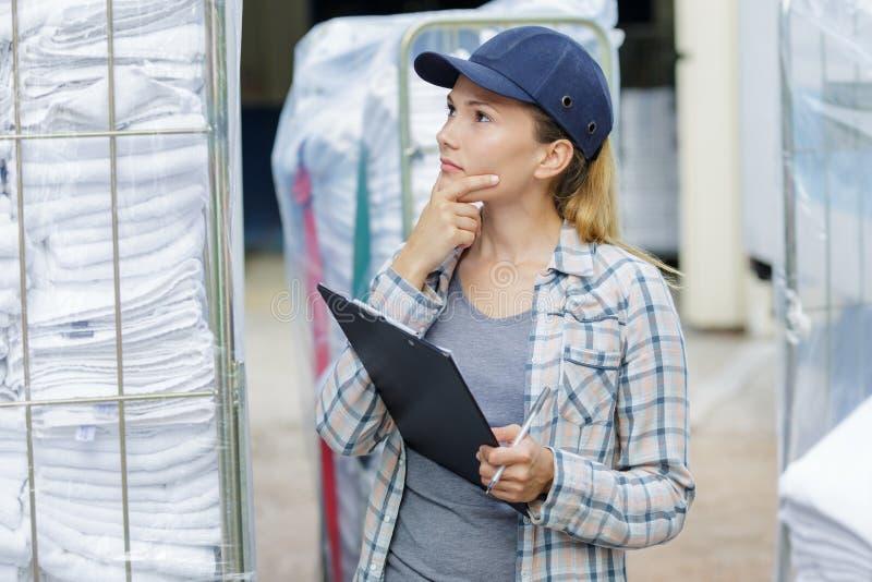 Θηλυκός κατάλογος γραψίματος εργαζομένων και σκέψη στην αποθήκη εμπορευμάτων στοκ εικόνα