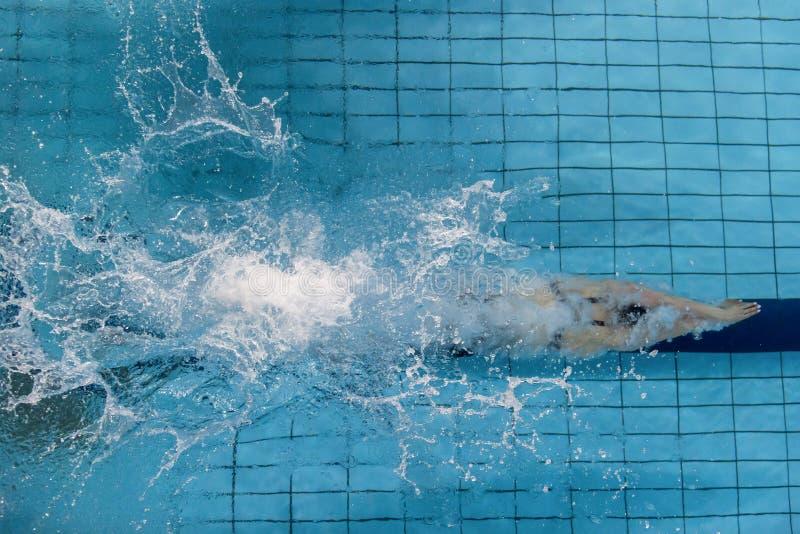 Θηλυκός κολυμβητής, ο οποίος πηδώντας και βουτώντας στο εσωτερικό αθλητικό swimmi στοκ φωτογραφία