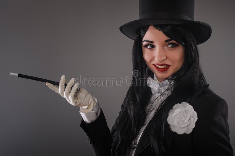 Θηλυκός μάγος στο κοστούμι κοστουμιών με το μαγικό ραβδί που κάνει το τέχνασμα στοκ φωτογραφίες με δικαίωμα ελεύθερης χρήσης