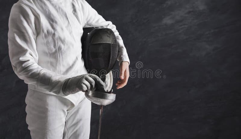 Θηλυκός ξιφομάχος στο άσπρο περιφράζοντας κοστούμι στο μαύρο υπόβαθρο στοκ εικόνες