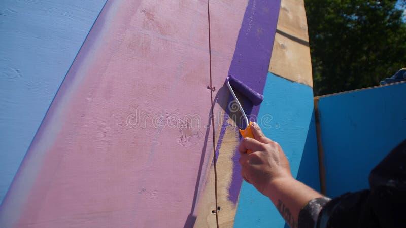 Θηλυκός ξύλινος τοίχος χρωμάτων χεριών στο μπλε χρώμα που χρησιμοποιεί τον κύλινδρο ζωγραφικής Ζωγραφική του ξύλου με το άσπρο σπ στοκ φωτογραφία με δικαίωμα ελεύθερης χρήσης