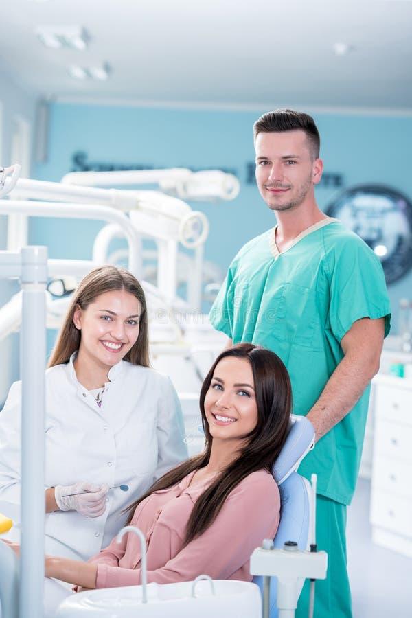 Θηλυκός οδοντίατρος, θηλυκό υπομονετικοί και βοηθός που χαμογελά μετά από τον έλεγχο στοκ φωτογραφία με δικαίωμα ελεύθερης χρήσης