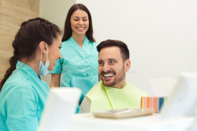 Θηλυκός οδοντίατρος που εξετάζει και που εργάζεται στο νέο αρσενικό ασθενή Γραφείο οδοντιάτρων ` s στοκ εικόνες