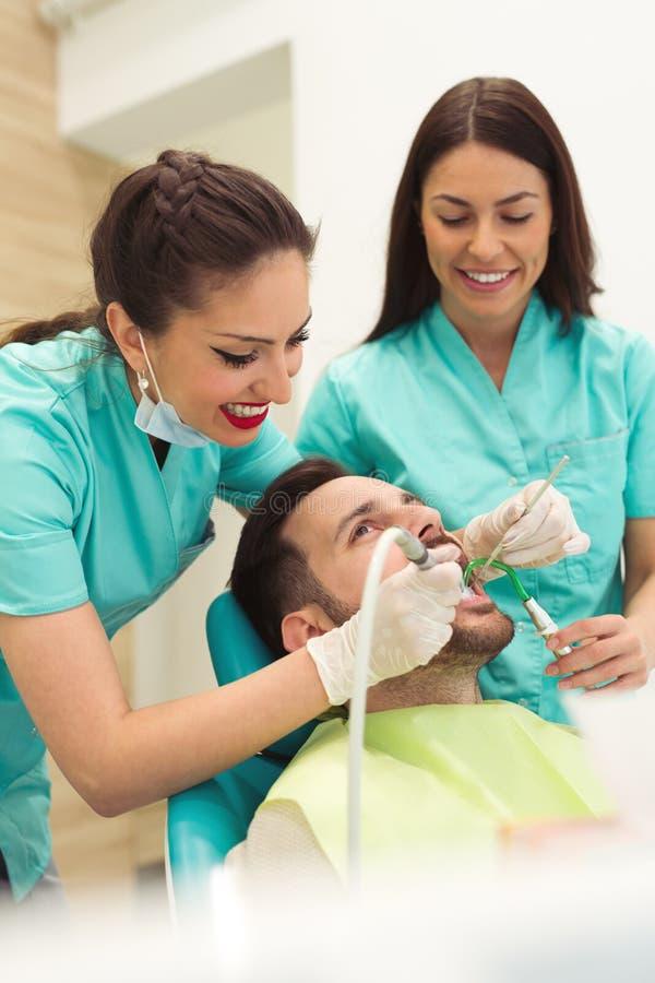 Θηλυκός οδοντίατρος που εξετάζει και που εργάζεται στο νέο αρσενικό ασθενή Γραφείο οδοντιάτρων ` s στοκ φωτογραφία