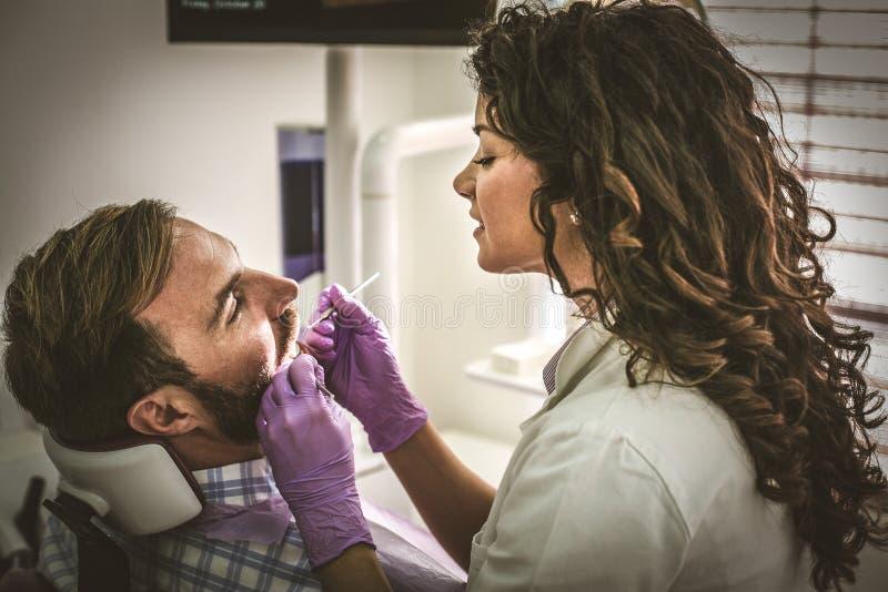Θηλυκός οδοντίατρος που εξετάζει το νεαρό άνδρα στοκ φωτογραφία