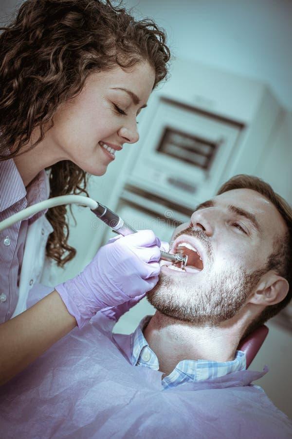 Θηλυκός οδοντίατρος που εργάζεται με το τρυπάνι οδοντιάτρων στον ασθενή στοκ εικόνες
