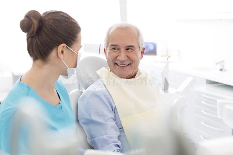 Θηλυκός οδοντίατρος που μιλά στο χαμογελώντας ανώτερο ασθενή στην οδοντική κλινική στοκ εικόνα με δικαίωμα ελεύθερης χρήσης