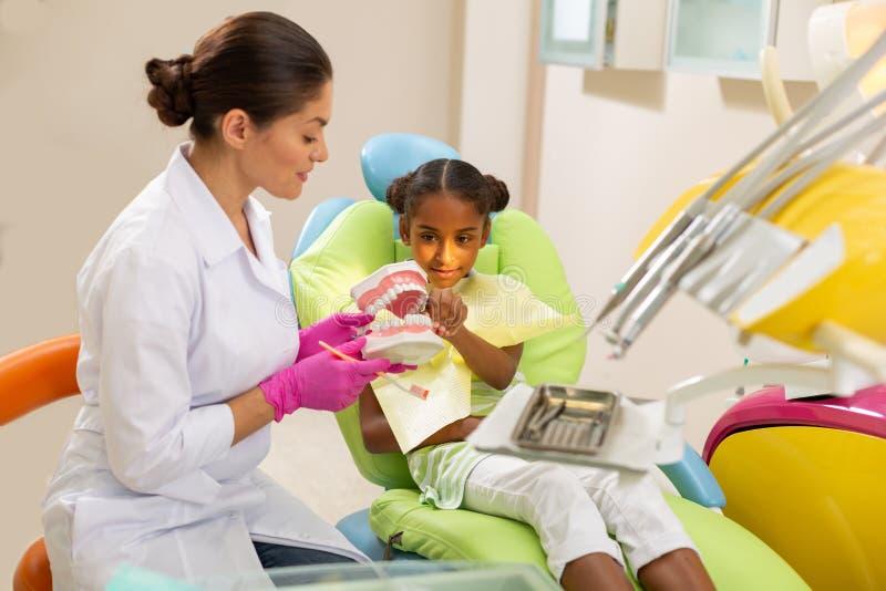 Θηλυκός οδοντίατρος που παρουσιάζει toothbrushing τεχνική στον ασθενή της στοκ εικόνα με δικαίωμα ελεύθερης χρήσης