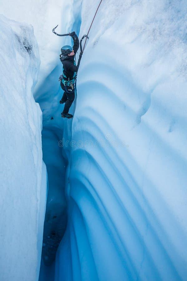 Θηλυκός ορειβάτης πάγου στο στενό φαράγγι στον παγετώνα Matanuska στοκ φωτογραφία