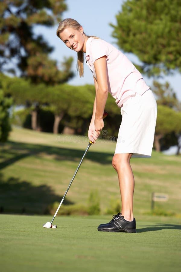 Θηλυκός παίκτης γκολφ στο γήπεδο του γκολφ στοκ φωτογραφία