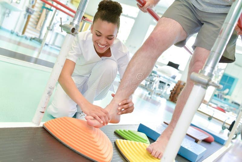 Θηλυκός παθολόγος που βοηθά τον ασθενή για να περπατήσει treadmill στοκ εικόνες