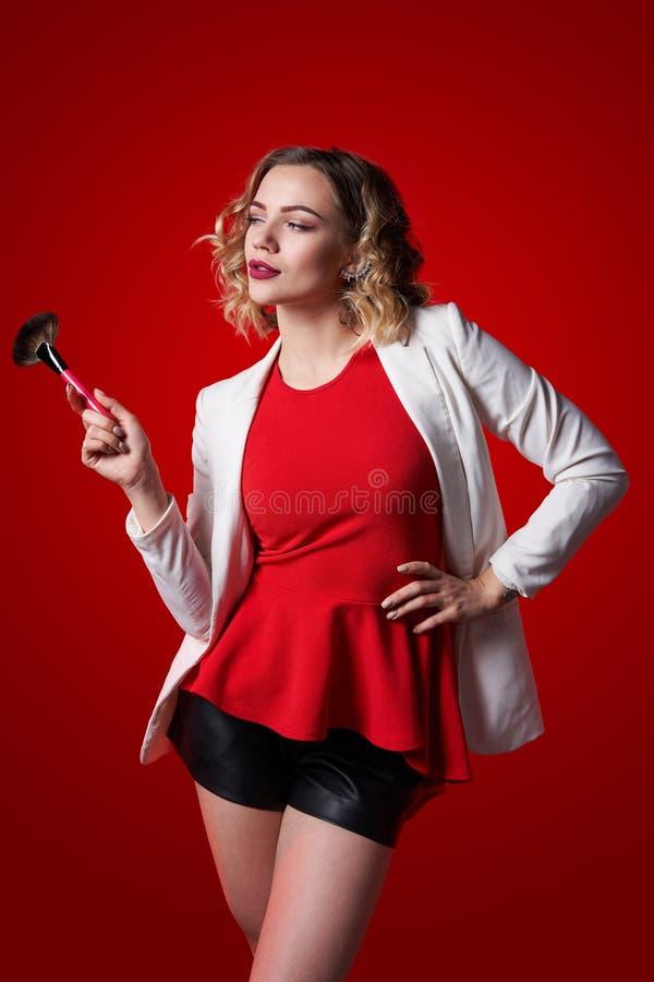 Θηλυκός στιλίστας που στέκεται με τη βούρτσα makeup πέρα από το κόκκινο υπόβαθρο στοκ φωτογραφίες