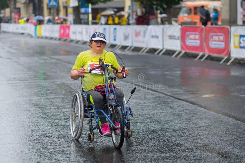 Θηλυκός συμμετέχων σε μια αναπηρική καρέκλα που πιέζει χρονικά στη γραμμή τερματισμού κατά τη διάρκεια της μισής φυλής μαραθωνίου στοκ φωτογραφία