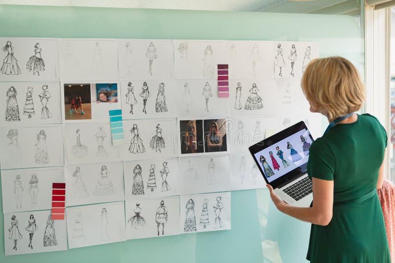 Θηλυκός σχεδιαστής μόδας που εξετάζει το σκίτσο κρατώντας το lap-top στο στούντιο σχεδίου στοκ φωτογραφία