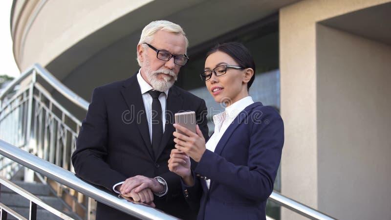 Θηλυκός σύμβουλος που παρουσιάζει στον παλαιό πολιτικό πιό πρόσφατες ειδήσεις στο τηλέφωνο, προεκλογική εκστρατεία στοκ εικόνα