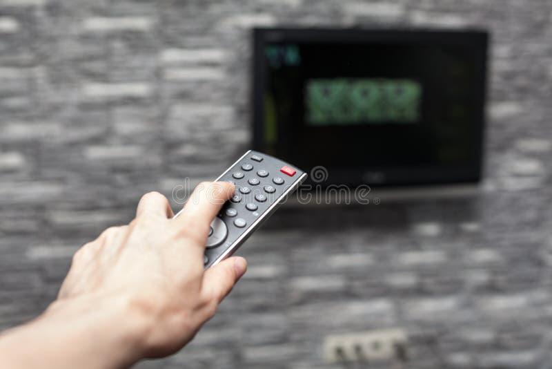 Θηλυκός τηλεχειρισμός TV εκμετάλλευσης χεριών και μεταβαλλόμενο ωθώντας κουμπί καναλιών στοκ φωτογραφίες