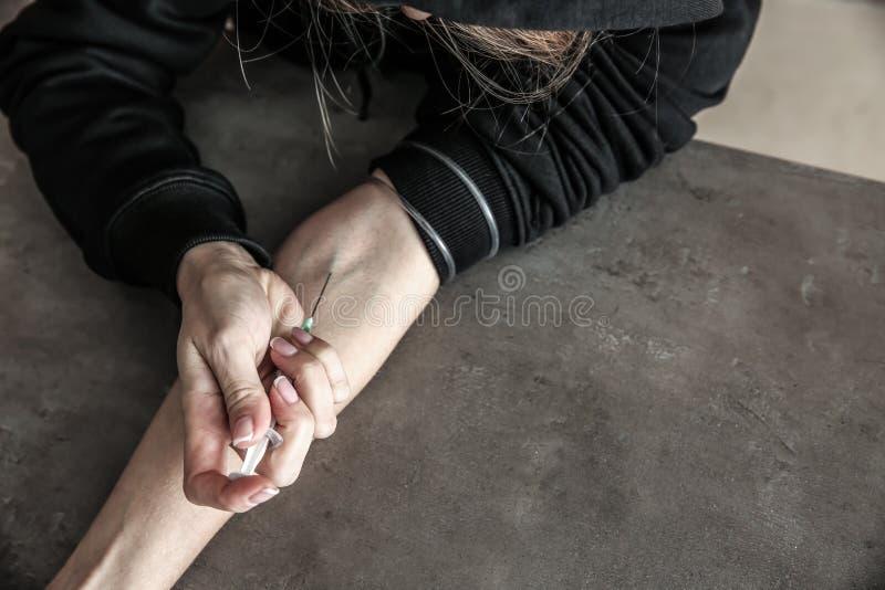 Θηλυκός τοξικομανής που κάνει την έγχυση στον γκρίζο πίνακα Έννοια του εθισμού στοκ φωτογραφία με δικαίωμα ελεύθερης χρήσης