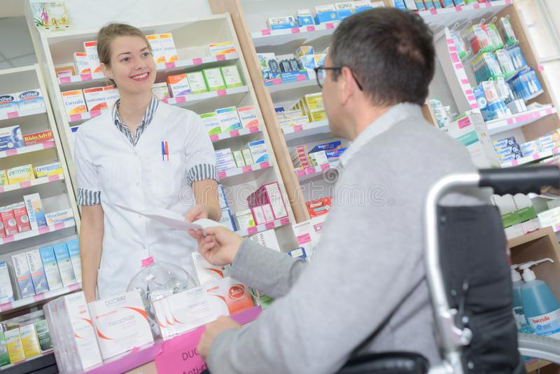 Θηλυκός φαρμακοποιός που παίρνει τη συνταγή από το με ειδικές ανάγκες άτομο στοκ φωτογραφίες