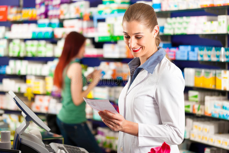 Θηλυκός φαρμακοποιός στο φαρμακείο της στοκ εικόνες